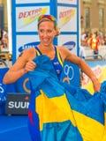 Stockholm - Lisa Nordén happy with the Swedish flag in her hand. STOCKHOLM - Aug, 24: A happy Lisa Norden raising the swedish flag, winner fo the Women ITU Royalty Free Stock Photos