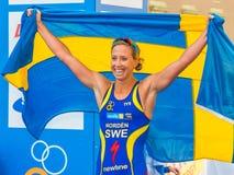 Stockholm - Lisa Nordén thru the finishline, happy with the Swe. STOCKHOLM - Aug, 24: Lisa Norden with the swedish flag, winner of the Women ITU World Triathlon Stock Photo