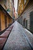 STOCKHOLM SVERIGE - AUGUSTI 20, 2016: Sikt av den smala gatan och c Royaltyfria Bilder