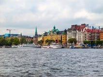 Stockholm/Sverige - Maj 15 2011: Sikt på pir med fartyg och de härliga byggnaderna av Stockholm royaltyfri bild
