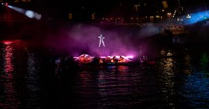 Hanging acrobat with the performance below in purple light stock photography