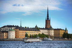 STOCKHOLM, SWEDEN - AUGUST 20, 2016: Tourists boat and View of G. Amla Stan from Stockholm City Hall  Stadshuset  in Stockholm, Sweden on August 20, 2016 Stock Photos