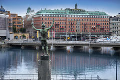 STOCKHOLM, SWEDEN - AUGUST 20, 2016: View of luxury hotel Grand. Hotel at Stockholm waterfront and Sun Singer Statue at Stromparterren Park from Norrbro in Stock Photos