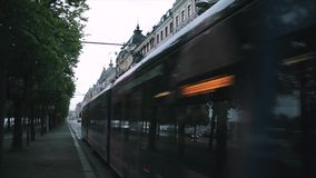 Stockholm, Sweden. A tram travels along the street with cars. Stockholm, Sweden. A car travels along the street stock footage