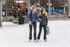 Two girls skating at a public ice skating rink outdoors. Royalty Free Stock Photos