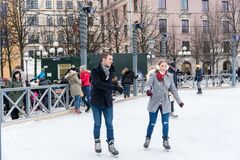 Young couple skating at a public ice skating rink outdoors in the city. Royalty Free Stock Photos