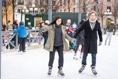 Young couple skating at a public ice skating rink outdoors in the city. Stock Images