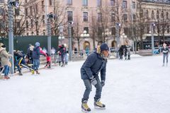 Young man skating at a public ice skating rink outdoors in the city. Stock Photos