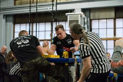 Two male arm wrestlers and referees in a tough fight. STOCKHOLM, SWEDEN - JANUARY 13, 2018: A Swedish and Latvian male arm wrestler and referrees in a match at Stock Photos