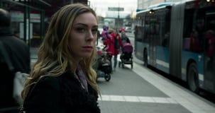 STOCKHOLM, ZWEDEN - NOVEMBER 26, 2018 - Jonge vrouw die bij busstop wachten stock footage