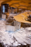 Stocking cookie cutter on marble slab. A metal cookie cutter sits on a marble slab with a bit of flour and some remaining dough in the background Royalty Free Stock Photo