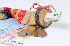 Stocking for saving with Euro bills and Euro Coins. In front off a white background Stock Photos