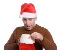 Stocking Stuffer. A young man wearing a Santa hat is looking inside his Christmas stocking and looks surpised, isolated against a white background Royalty Free Stock Image
