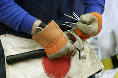 Stocking Up on Supplies. A pair of gloved hands holding a hammer and filling work apron pockets with nails Stock Images