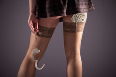Stockinged legs with handcuffs and dollars Royalty Free Stock Images