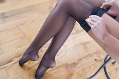 Stockings. Young woman who puts her stockings stock photo