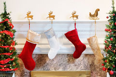 Stockings by the fire. Four Christmas stockings hanging on the mantelpiece Stock Images