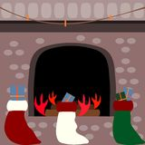 Stockings full of gifts in front of a fireplace Stock Photos