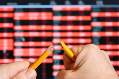 Stockmarket crash, broken pencil. Stock market screen with falling share prices,snapping pencil with stress stock photo