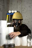 Stockpiling. Woman dressed in gas mask and hard hat hiding in the basement with stockpiled goods Stock Image
