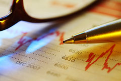 Stocks. Pen on newspaper stock performance graph.  Toned image, soft focus Stock Photo