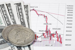 Stocks and cash. A stock market trend printout with paper and silver US currency Stock Image