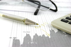 Stocks and Shares. Stock market data with a pen and calculator and the word buy written on the report Royalty Free Stock Photography