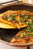 Stodgy Spanish potato tortilla with herbs in black pan Royalty Free Stock Photo