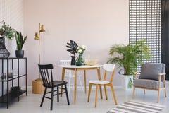 Stoel bij houten lijst met bloemen in eetkamerbinnenland met leunstoel en gouden lamp Echte foto stock foto