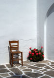 Stoel en geraniums - Paros Stock Afbeelding