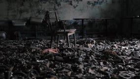 Stoel onder honderden oude gasmaskers in een verlaten gebouw in Tchernobyl, Pripyat, de Oekraïne stock video