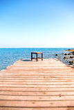 Stoel op het houten dek door het overzees stock foto