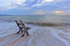 Stoel op het overzeese zand met lang snelheidsblind Royalty-vrije Stock Foto