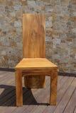 Stoel van stevig hout op een steenachtergrond die wordt gemaakt Stock Foto