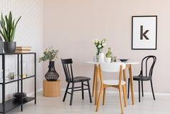 Stoelen bij houten lijst met bloemen in eetkamerbinnenland met installaties en affiche Echte foto stock fotografie
