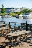 Stoelen en lijsten van lokaal restaurant in haven met boten royalty-vrije stock afbeeldingen