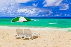 Stoelen en paraplu bij tropisch strand Stock Afbeelding