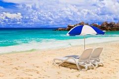 Stoelen en paraplu bij tropisch strand stock afbeeldingen