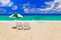 Stoelen en paraplu bij tropisch strand Royalty-vrije Stock Afbeelding