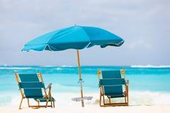 Stoelen en paraplu op tropisch strand Stock Afbeeldingen