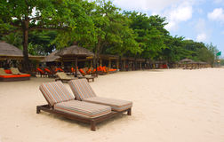 Stoelen en paraplu's op strand Royalty-vrije Stock Afbeeldingen