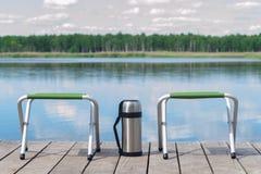 stoelen en thermosflessen op de achtergrond van de rivier royalty-vrije stock afbeelding