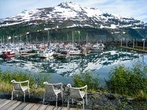 Stoelen met de mening van Whittier-haven in Alaska Stock Afbeeldingen