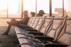 Stoelen met passagiers bij de luchthaven stock foto