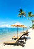 Stoelen op het strand dichtbij met overzees Royalty-vrije Stock Afbeeldingen