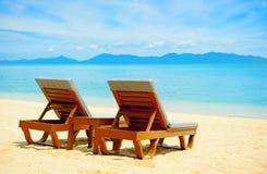 Stoelen op het strand dichtbij met overzees Royalty-vrije Stock Foto