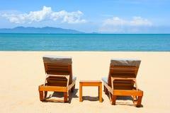 Stoelen op het strand dichtbij overzees Stock Fotografie