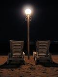 Stoelen op nachtstrand royalty-vrije stock afbeelding