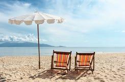 Stoelen op strand dichtbij het overzees Stock Fotografie