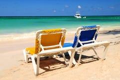 Stoelen op zandig tropisch strand stock foto's